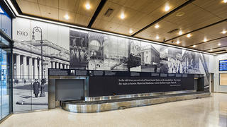 View of the Baggage Claim at Moynihan Train Hall with a mural containing the historical timeline of the building.