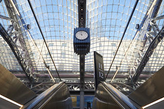 View of the clock at Moynihan Train Hall from the angle of a passenger coming up the escalator from the tracks.