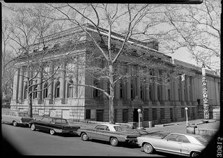 Image of a building in New York City with a totem pole on the right side. This used to be the home of the Museum of the American Indian in 1963.