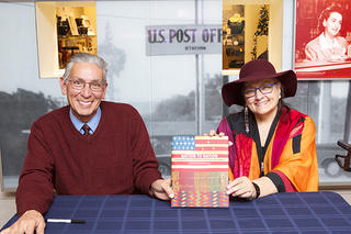 Two people, Cheyenne and Hodulgee Muscogee writer and advocate, Suzan Shown Harjo, and Kevin Grover, former director of NMAI  with a book for the Nation to Nation exhibition in between them.