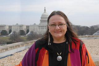 A smiling woman (Suzan Harjo) standing on top of a building (the National Museum of the American Indian) with the United States Capitol Building in the background.
