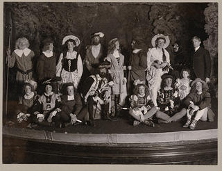 A view of a group of boys on a stage dressed in clothes that are in the style of colonial Britain.