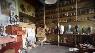 An interior room with a display of various pieces of sculpture and art.