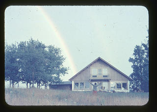 A picture of a rainbow over Hilltop House and Stuido with a woman, Dorothy Riester celebrating below.