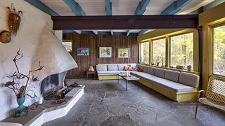 View of a living room with a white concrete fireplace built by Dorothy Riester.