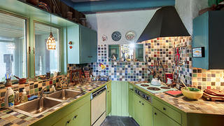View of a kitchen with colorful tiles that are reminiscent of the tilework and color of Midcentury architecture.