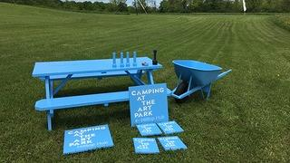 A blue table and chairs with various signage that says Camping at the Art Park.