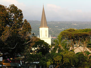View of the Mokuaikaua Church Steeple in Kailua-Kona Hawaii with trees in the foreground