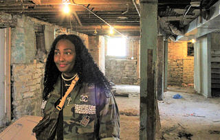A woman standing in the foreground of the interior of a building that is in the process of rehabilitation.