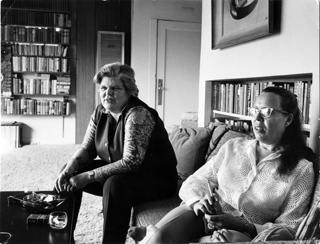 Image of two women sitting on a couch with a bookshelf in the background.