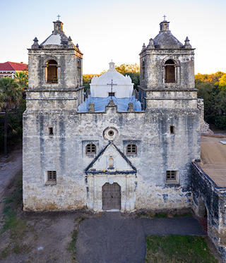 Exterior front facing view of Mission Concepción, an old Spanish style mission in San Antonio, Texas.