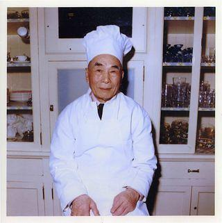 A man, Kee Low, sits in front of cabinets dressed in the white jacket and hat typical of a chef.