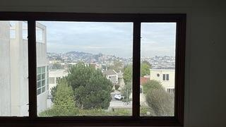 View out of a large picture window where, since the home is on a hill, you can see the man buildings of San Francisco below.