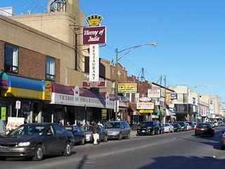 View of a busy street in Chicago filled with stores that serve Indian and other South Asian specialties.