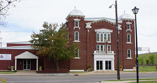 A view of a brick church in the Greenwood District of Tulsa, Oklahoma. The chapel is on the right side with white trim and stained glass windows, with an shorter hall on the left.