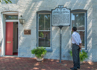 A close up of a brick building with a red door. On the right side of the image is a man reading a historic marker describing the history of the building.