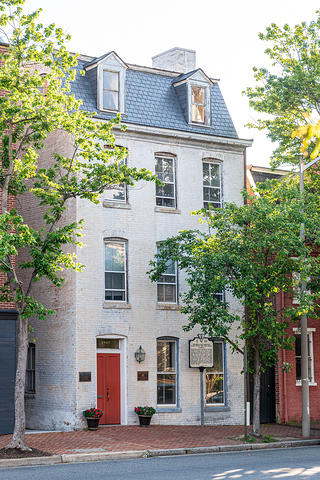 Exterior view of a brick rowhouse in Old Town Alexandria with trees along the street.