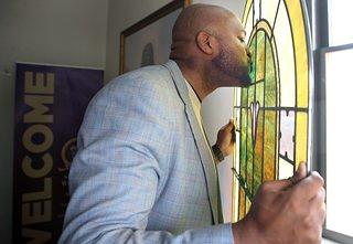 Man kissing a yellow stained glass window at the Historic Vernon AME in Tulsa, Oklahoma.