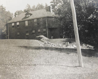 A black and white image of a two story building with some grass and a pole in the foreground.