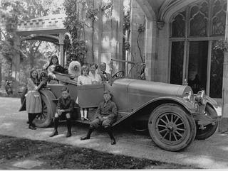 Helen Gould's family, which includes three young girls and two boys in an old car from the 1900s. With them are three dogs of varying breeds and sizes.