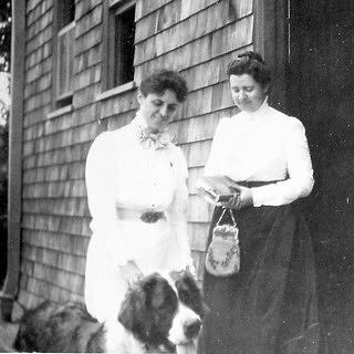 Two women with a St. Bernard, standing in front of a building with wooden siding.