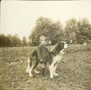 In nearly sepia toned image, a young boy standing next to a St. Bernard dog that is almost the same height as him. They are in the middle of a grassy field.