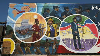 A detailed view of the mural Absolute Equality. This section depicts the transatlantic slave trade through a image of a globe, enslaved people shackled together in chains, Harriet Tubman, and Mustafa Zemmouri.
