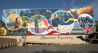A full view of a mural with four circles depicting Black History in Galveston throughout time.