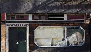Exterior view of a building in Harlem with paper covering the windows and a ghost sign that reads Lenox Lounge in large letters.