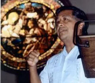 Cesar Chavez standing at a podium with a circular stained glass window behind him. The angle of the photograph is from below Chavez looking up.