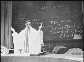 A man standing in front of a large chalk board with his hands outstretched in sermon. He is wearing the white robes with stripes in front.