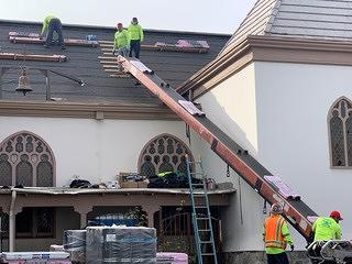 Two men working on wood framing inside the Los Angeles Church of the Epiphany. On the right you can see a short hallway with white walls.