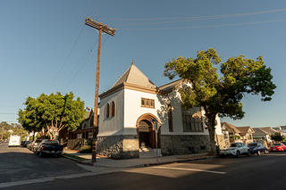 A wide angle exterior view of the Los Angeles Church of Epiphany, a white building with brown trim. There is an electrical pole in front of the building along with some greenery.
