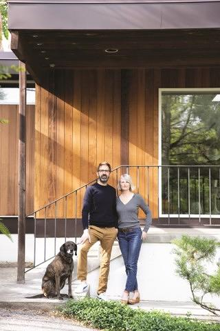 The couple standing beside each other outside of their house, with their brown dog.