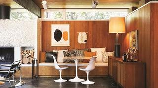 Interior dining room with wood paneled walls and décor featuring orange, black, and white patterns.