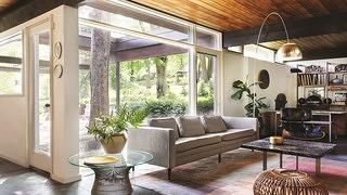 A sunny living room featuring gray and white-toned furniture and large windows that look out into the garden.