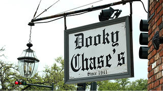 Close up of a sign that says Dooky Chase's since 1941. There is an lantern hanging off the sign with a metal frame. The words are black on a white background and attached to a brick building.