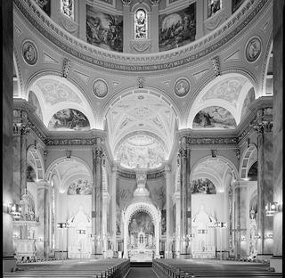 Interior of the main sanctuary in a cathedral with pews on either side of a central aisle beneath a soaring dome with ornate work. The image is black and white and was taken as part of HABS documentation.