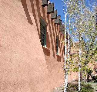 The exterior wall of a church in New Mexico is made of a sandy brown stucco in the Pueblo Revival-style of architecture.