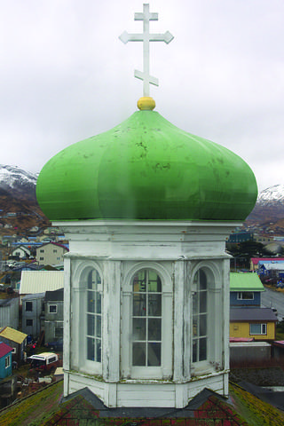 A close up photograph of a green dome of a church against a gray sky.