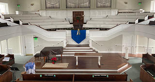 Interior of a meetinghouse, the images shows a balcony with pews arranged in a curved design while other seating surrounds a stage with a covered piano and a table.
