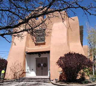 The exterior view of a church New Mexico is made of a sandy brown stucco in the Pueblo Revival-style of architecture. The front of the building is partially obscured by a tree branch, but  there is a central doorway with stairs leading to the entrance.