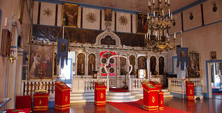Ornate interior of a church with Indigenous Aleut woodworking with design work traditionally seen in Russian Orthodox churches. The iconostasis has white and gold detailing with a series of red podiums to holding icons and other sacred objects.