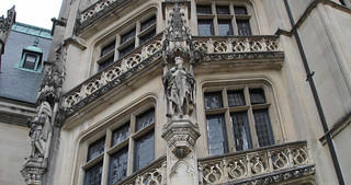 Close up view of the architectural details at a grand estate. Ornate stone carvings and architecture indicate the opulence of the manor.