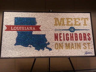 A sign made of beads that welcoming attendees to the 2013 Main Street's Conference. It reads Lousiana Meet the Neighbors on Main Street.