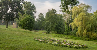 A view of the David Hartt exhibition shows the oval landscaping of flowers against the background of the broader Glass House grounds. The garden is along a hillside, hugging the land.