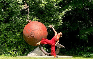 A woman in a red jumpsuit dancing to mirror a modern sculpture which consists of a red ball on a platform amidst a grassy space.