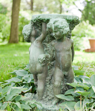 An image of a sculpture of three dancing children surrounded by lush green foliage.