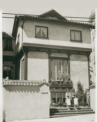 Black and white image of the Japanese YWCA building in San Francisco. There are two windows on the upper floor and a much larger one with immediately in front of a set of stairs. Four people stand on the front stairs, two women and two young girls.