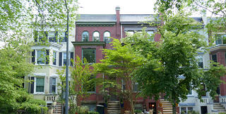 An image of a group of brick rowhouses in Washington, D.C. The Hurd House is the one in the middle, a red brick exterior with a green tree in front partially obscuring the facade.